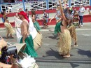 People in grass skirts following the band